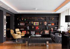 Integradas, as salas de estar e jantar têm paredes pintadas no tom grafite. De carvalho ebanizado, a estante traz iluminação embutida. Sofá da Artefacto, banco do Empório Beraldin e tapete da Avanti.