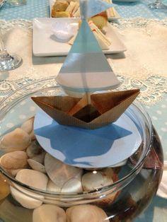 Centro de mesa con barquitos de papel, agua, caracoles.