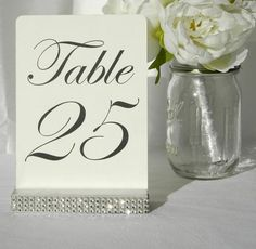 Silver table number holders, the holder has been wrapped with a crystal wrap ribbon (please note: The crystal wrap does NOT include real diamonds, crystals, or