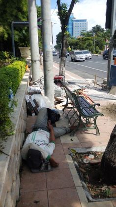 With his sandals as pillow, he spended his break by napping. That day he was fasting during the month of Ramadhan in June 2016. He was fixing the pedestrian infront of a luxurious hotel #pedestrian #surabaya #worker #fasting #nap