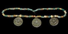 VIKING BEAD NECKLACE WITH PENDANTS 11th-12th century AD  A restrung necklace of mainly spherical and tubular glass beads with three discoid bronze pendants, each with raised border, band of pellets surrounding a central boss. 51 grams, 44cm