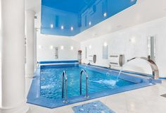 All white indoor pool with white column and blue roof above the pool.  Pool includes silver fountain spout in one corner.