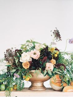 Loose centerpieces with greenery-- this one is more orangey than pink/red, but has different tones