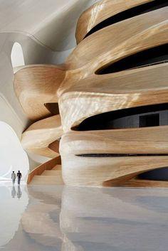 La sinuosa scala dell'Opera di Harbin, nel nord della Cina, progetto frutto di un concorso internazionale del 2010: realizzata dallo studio Mad Architects. 8500 metri quadrati di struttura, tanto legno...