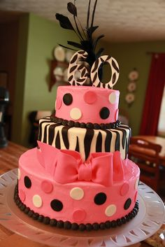 60th birthday cake in pink, white, and black! Top tier German chocolate with coconut-pecan filling; middle tier chocolate hazelnut with chocolate hazelnut filling; bottom tier butter cake with buttercream. All covered with vanilla buttercream. Fondant zebra stripes and polka dots, gum paste bow and number.