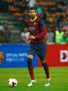 Gerad Pique runs with the ball during the friendly match between FC Barcelona and Malaysia at Shah Alaml Stadium on August 10, 2013 in Kuala Lumpur, Malaysia.