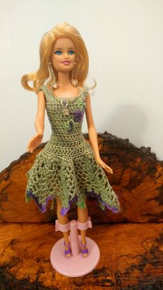 Barbie is wearing a sage green dress trimmed in purple. She has a complete outfit with her panties, jewelry, and shoes. Barbie Beach doll is included.