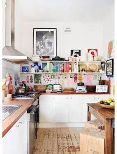 Colourful accessories add interest to a simple modern kitchen. This Bohemian style influence is achieved by creating a focal point at the splash back area with an eclectic mix of items.