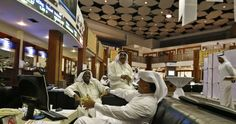 Investors share a laugh as they monitor stocks at the Dubai Financial Market, June 17, 2013. The United Arab Emirates has revived a proposal to merge its two main stock exchanges in a state-backed deal that could boost trade in the local market and attract more foreign investment to the Gulf state, sources familiar with the plan said. REUTERS/Jumana El Heloueh (UNITED ARAB EMIRATES - Tags: BUSINESS) - RTX10QOR