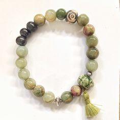 Made of jade kaki beads, one kaki skull and pompom. Bracelet composé de perles de jade vert kaki, une tête de mort en porcelaine kaki et pompom.