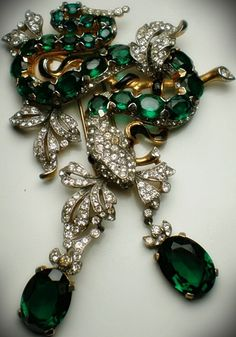 Alfred Philippe for Trifari, 1941. Cast in rhodium with multifaceted green crystal stones, cabochon-cut red stones eyes, pavé crystals. From the line inspired by the Empress Eugenia.