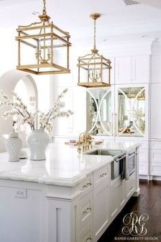 Stunning white transitional kitchen with brass chandeliers faucets pot filler and handles. Two-toned La Cornue stove. Stunning white transitional kitchen with brass chandeliers faucets pot filler and handles. Two-toned La Cornue stove. Kitchen Nook, White Kitchen Cabinets, New Kitchen, Kitchen Interior, Kitchen White, Kitchen Ideas, Kitchen Themes, Island Kitchen, Kitchen Sinks