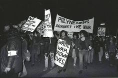 John Miller, photo // Tigilau Ness in the centre with the sign 'White War, Brown Lives'