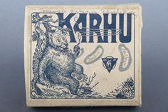 Forssan museo. Oy Helsingin savuke- ja hylsytehtaan Karhu-savukerasia. Kannen etiketissä on kuvituksena puuhun nojaava, tupakkaa polttava, istuva karhu painettuna sinisellä valkoiselle paperipohjalle. Etiketin ylälaidassa lukee isolla tuotteen nimi: KARHU, myös sinisellä painettuna. Kannen etulaidassa on tehtaan nimi: OY HELSINGIN SAVUKE JA HYLSYTEHDAS. Rasiassa ei ole sinettiä. Pakkaus on täynnä lyijykynällä, kaunolla kirjoittaen tehtyjä merkintöjä.
