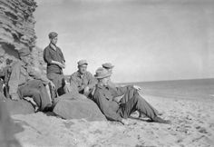 A group of American soldiers relax in the sunshine on the sand at Burton Beach, just south of Burton Bradstock in Dorset. Amongst the group looking out to sea are: Pfc James Crane (from Harding, Missouri), Private Stanley T Miller (from Axtel, Kentucky), Pfc W W Johnson (from Bluefield, West Virginia), T/5 G R Miller (of 4106 Vermont Avenue, Louisville, Kentucky) and T/4 George Keister (from Fort Wayne, Texas). The ridged rock of Burton Cliff can be seen behind them on the left of the photograph