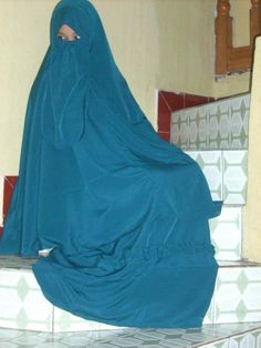 A Muslim woman wearing a beautiful turquoise niqab out of choice