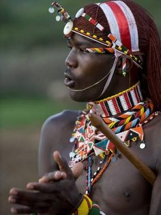 Photographic Print: Kenya, Laikipia, Ol Malo; a Samburu Warrior Sings and Claps During a Dance by John Warburton-lee : 24x18in