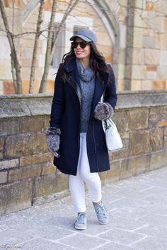 Navy wool coat, grey turtleneck, white jeans, grey sneakers, baseball cap, Furry Mittens, winter outfit