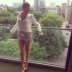"""Fashion-Looks: """"Düsseldorf"""" kommentiert die Sängerin ihren Post auf Instagram und präsentiert sich im klassisch eleganten Look mit ihrem Lieblingskleidungsstück, der Bluse, und einer hochgeschnittenen Shorts kombiniert zu nudefarbenden Heels."""