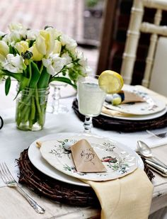 A spring/early summer table setting complete with elegant little candy mint favors wrapped in petite paper bags...