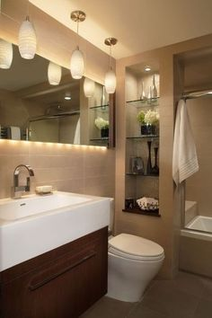 Natural flax-colored large format tiles and simple textured light fixtures dress a transitional feeling bathroom. The blend of thoughtful design — such as the lighting tucked behind the mirror — and a monochromatic tile palette are what support the transitional look.