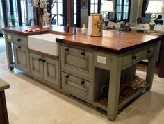 The cabinets were custom made in England, painted with Farrow & Ball's French Gray, and glazed. Natural pine base cabinets flanking the range are also glazed, and topped by honed Golden Leaf granite