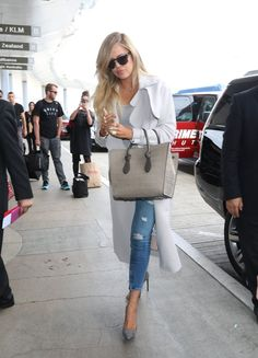 Pin for Later: We Just Can't Figure Out Kim's Latest Accessory At the airport, Khloé paired a sophisticated white coat and structured bag with ripped jeans.