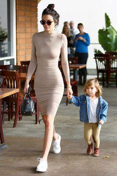 Kendall Jenner - vestido ajustado con cuello alto de color nude, de Ana & Elsa; zapatillas blancas, de Kenneth Cole; bolso de cuero Lucrezia, de Givenchy; y gafas de carey, de Dior.