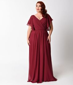 This stunning plus size burgundy dress is flowy with short flutter sleeves. It has a wrapped v-neckline and removable tie-up waist belt. The bodice has built in boning and cup padding for additional support.
