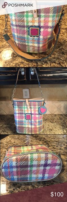 """Dooney & Bourke spring plaid pre loved Dooney Bourke spring plaid purse so detail shoulder purse pre loved slight wear on leather trim around bottom coated canvas scallops around top perfect scallops around a little flip up but doesn't effect anything . Inside a little dirty and ink spots one in the bottom and across small pockets but overall a beautiful bag.10 1/2 tall 11"""" w bucket style❤️handle drop 10"""" Dooney & Bourke Bags Shoulder Bags"""