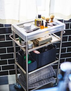 A bathroom trolley propped with mens grooming products, like shaving equipment and towels.