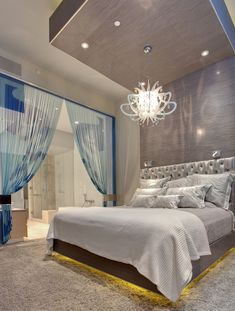 Wow lighting and sheer printed curtains cozy bed adjacent to bathroom. I want to take my honeymoon there.