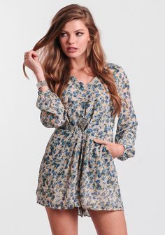 Cream-colored romper featuring subtle pleating at the waist for added flair and a ditzy floral print in hues of blue, navy, white, and green.