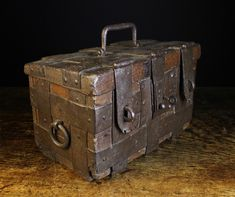 An Iron Bound Oak Strong Box, Circa 1500, of deep colour and patination. The rectangular chest clad in interwoven straps with a swing handle to the lid and side, and a lock with key flanked by padlock hasps to the front,  10 ins (25.5 cms) high [handle down], 16 ins (41 cms) wide, 10 ins (25.5 cms) deep.