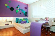 Projetado para uma mostra, este quarto utiliza elementos gráficos constrastantes e cores marcantes. O mobiliário branco e retilíneo se contrapõe ao roxo e, na parede acima da cabeceira, a arquiteta Julia Cruz fez uma composição com bastidores de bordado.