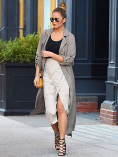 Chrissy Teigen wore a black top and baby bump-covering beige wrap skirt that she topped off with a gray trench coat in N.Y.C.