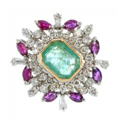 An emerald, ruby and diamond ring. The rectangular-shape emerald, with vari-cut diamond surround, and marquise-shape ruby accents. Estimated diamond weight 1.30cts. Weight 12.3gms