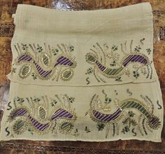 A women's 'uçkur' (sash / waist band), made of wild silk, with embroidered ends.  From the Aegean region, late-Ottoman era, early 20th century.  With the representation of four caterpillar-like creatures (probably silkworms), executed in 'two-sided embroidery' (front and rear are identical), using silk, metal thread and 'tel kırma' (motives obtained by sticking narrow metallic strips through the fabric and folding them).  (Source: AntikAda, Eskişehir).