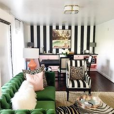 THIS WALLPAPER: Chic office boasts a black and white striped accent wall lined with pink cabinets and black countertops lit by a clover flush mount.
