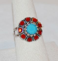 Mariana Jewelry  Gypsy Soul Flower Ring - R7211  $37   Bevel cut center turqoise colored bead surrounded by red crystals.  Plated in 925 sterling silver.  Adjustable sizing.