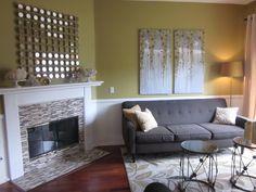 living rooms - Behr - desert moss - corner fireplace, gray tufted sofa, charcoal gray sofa, art over sofa, art above sofa, mosaic tiled fire...