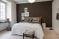 Offset artwork above bed.Chocolate brown and white room.