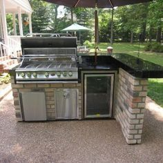 This L-shaped outdoor kitchen features a bar counter sitting area. Besides the grill, the unit also includes a built-in wine cooler.