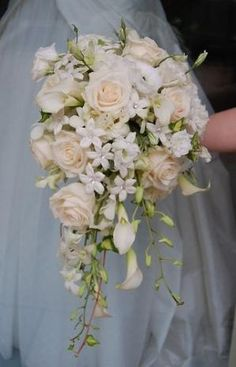 Cascade Bridal Bouquet White flowers such as roses, mini callas, stehanotis and orchid create this simple but elegant bridal bouquet by jodi