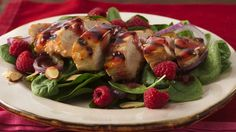 An organic raspberry-spread vinaigrette glazes grilled chicken and dresses the spinach-and-raspberries base of a delightful main-dish salad.