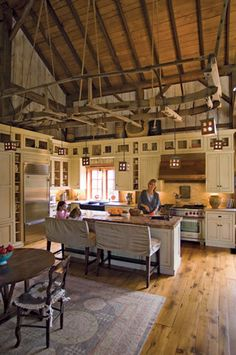 interesting how they have a dropped-looking ceiling thing hanging over this restored old barn kitchen.