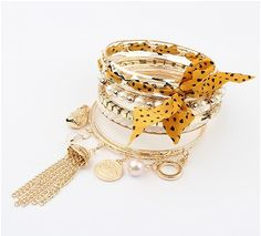 Multi-bangle Bracelet with statement yellow polka dot ribbon and charm trinkets. #Bejeweled