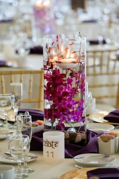 purple wedding centerpiece: floating candle twinkles above submerged orchids / Koru Wedding Style: {Purple & Gold Vermont Wedding} Mala & Colin