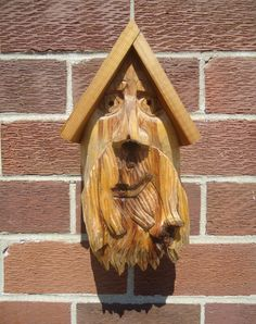 Beautiful cedar wood birdhouse, showing a hand carved old man face with the bird's entry point being though his nose. on Etsy, $95.00