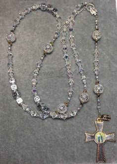 Two-tone Rosary made with Swarovski® crystals. You may personalize this Rosary with up to 5 words and up to 10 letters each. Please enter the word(s) exactly as you'd like to have on the Rosary and wh
